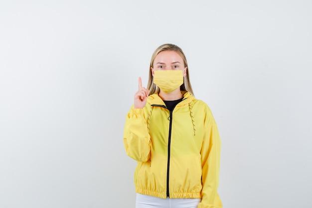 Junge dame zeigt in jacke, maske und sieht vernünftig aus. vorderansicht.