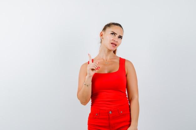 Junge dame zeigt in rotem unterhemd, roter hose und sieht nachdenklich aus. vorderansicht.