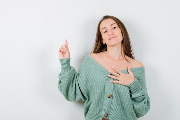 Junge dame zeigt nach oben, hält hand auf brust in wolljacke und sieht stolz aus. vorderansicht.