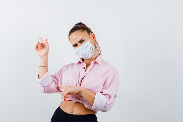 Junge dame zeigt nach oben und links in hemd, maske und nachdenklich aussehend, vorderansicht. Kostenlose Fotos