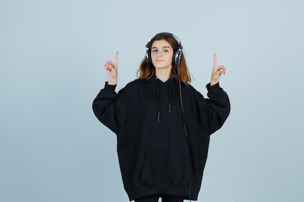 Junge dame zeigt nach oben, während sie musik mit kopfhörern in übergroßem kapuzenpulli, hosen und selbstbewusstem blick von vorne sieht.