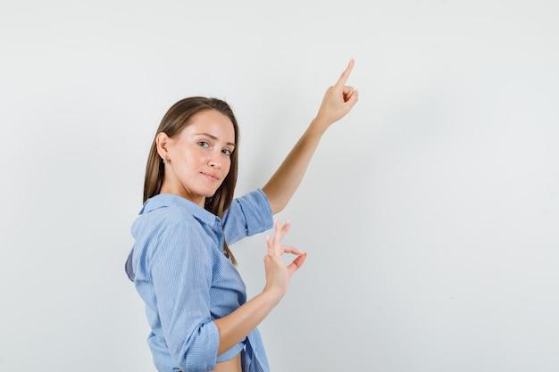 Junge dame zeigt nach oben, während sie ok zeichen im blauen hemd zeigt und erfreut aussieht.