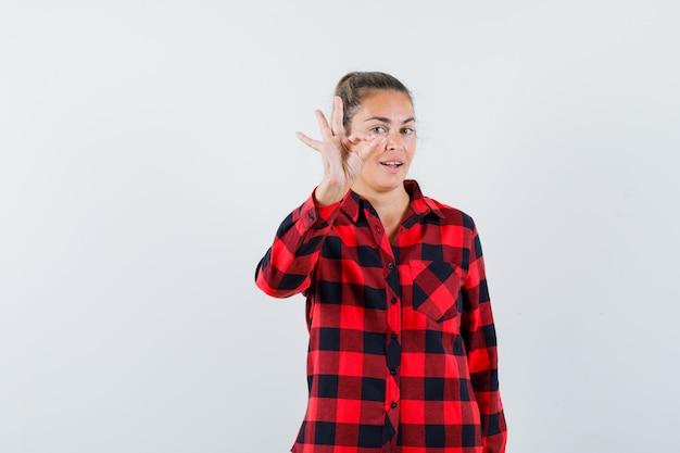 Junge dame zeigt ok geste im karierten hemd und sieht fröhlich aus
