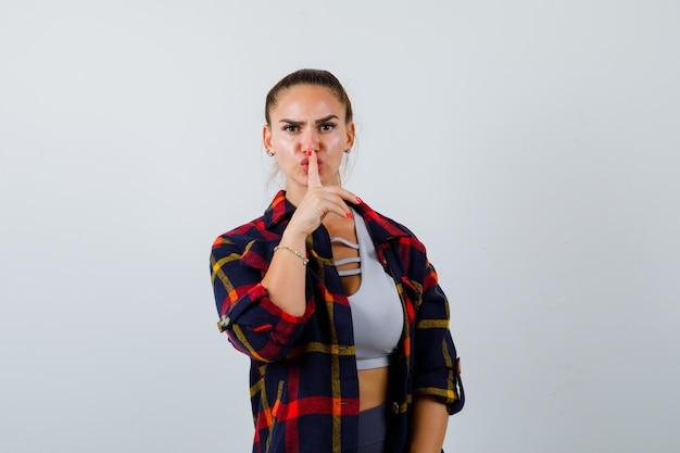 Junge dame zeigt stille geste in top, kariertes hemd und sieht ernst aus, vorderansicht.