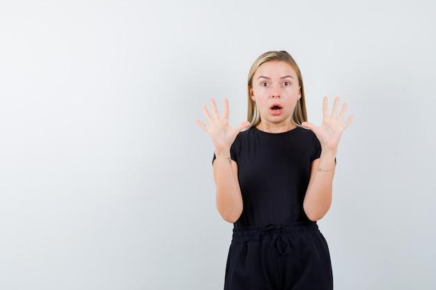Junge dame zeigt stoppgeste in t-shirt, hose und sieht überrascht aus. vorderansicht.