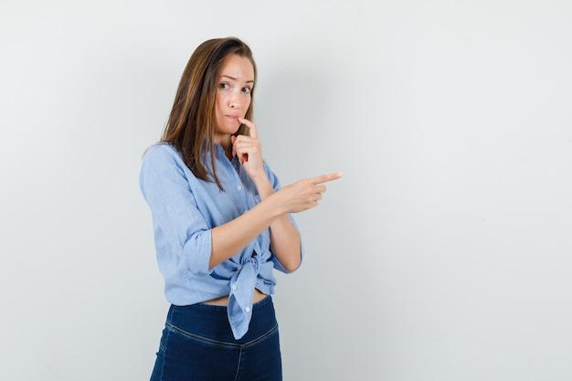 Junge dame zeigt zur seite in blauem hemd, hose und schüchtern