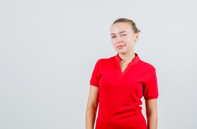 Junge dame zwinkert auge im roten t-shirt und schaut selbstbewusst