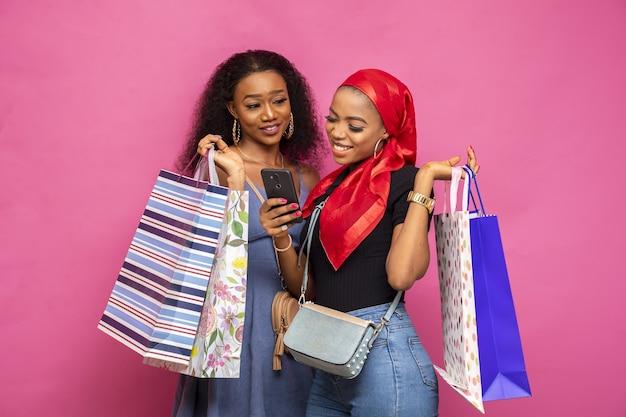 Junge damen, die etwas auf einem handy ansehen, während sie einkaufstüten tragen
