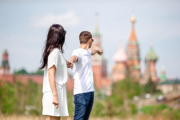 Junge datierungspaare in der liebe, die in stadthintergrund st.-basilikum-kirche geht