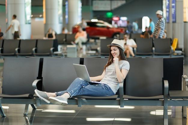 Junge denkende reisende touristenfrau mit hut, die am laptop arbeitet, während sie in der lobbyhalle am internationalen flughafen wartet?