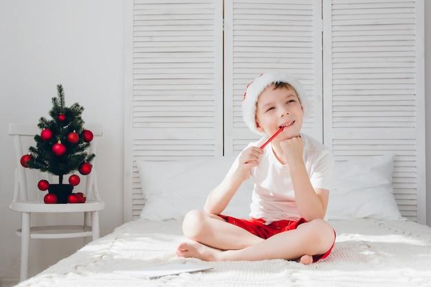 Junge denkt an den brief an den weihnachtsmann