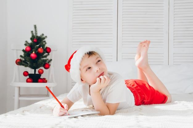 Junge denkt, er würde den brief an den weihnachtsmann schreiben