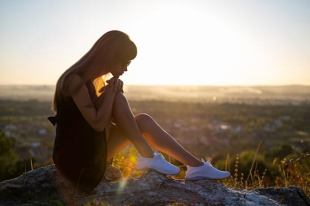 Junge depressive frau im schwarzen kurzen sommerkleid sitzt auf einem berghügel und denkt im freien bei sonnenuntergang. einsame frau, die an einem warmen abend in der natur nachdenkt.