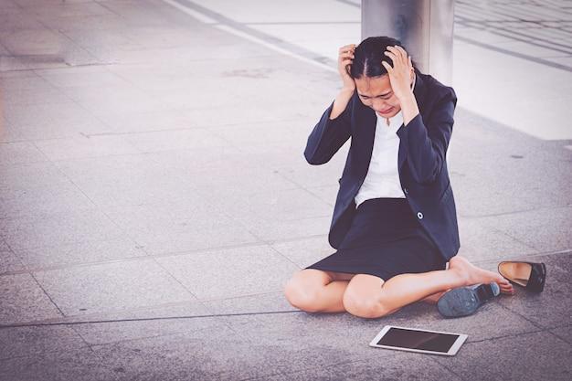Junge deprimierte geschäftsfrau, die auf dem boden sitzt
