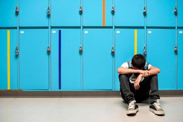 Junge, der allein stillstehenden kopf auf seinen armen sitzt