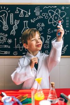 Junge, der als chemiker verkleidet ist und ein reagenzglas sieht, das mit einem chemiespiel vor einer tafel mit zeichnungen spielt