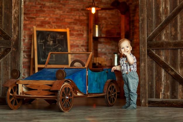 Junge, der am mechaniker mit retro- auto der werkzeuge nahe der garage steht