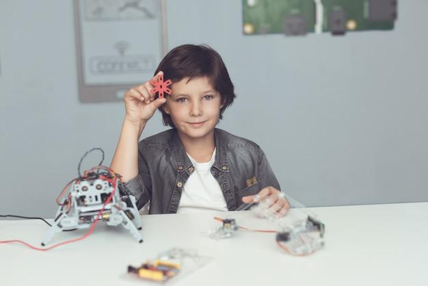 Junge, der am schreibtisch sitzt und zu hause roboter konstruiert