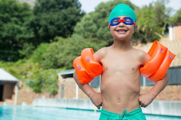 Junge, der armbänder am pool steht