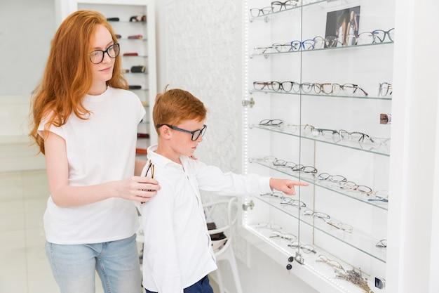 Junge, der auf brillen bei der stellung mit weiblichem optiker im optica zeigt