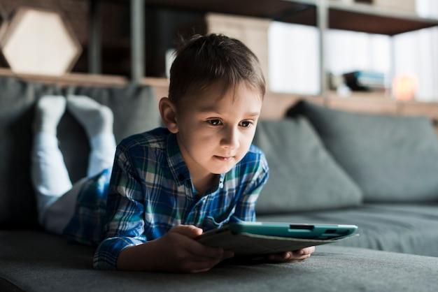 Junge, der auf couch mit tablette liegt