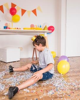 Junge, der auf dem boden spielt mit papierkonfetti nach parteifeier sitzt