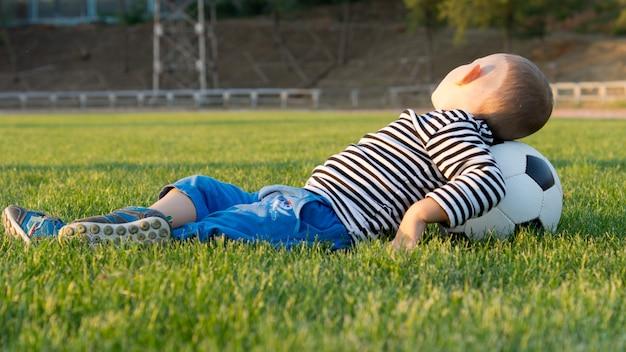 Junge, der auf dem gras in einem park liegt, der seinen kopf auf einem fußball oder fußball ruht