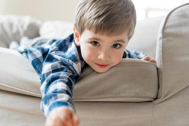 Junge, der auf dem sofa mittlerer schuss spielt