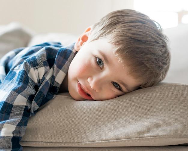 Junge, der auf dem sofa nahaufnahme spielt