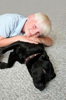Junge, der auf den hund, lächelnd, porträt liegt