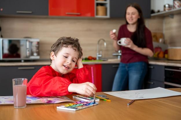 Junge, der auf der küche zeichnet, während mutter tee oder kaffee trinkt