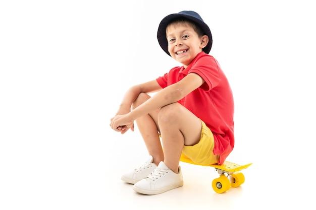 Junge, der auf einem gelben skateboard sitzt