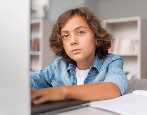Junge, der auf einem laptop aufpasst, um seine hausaufgaben zu machen
