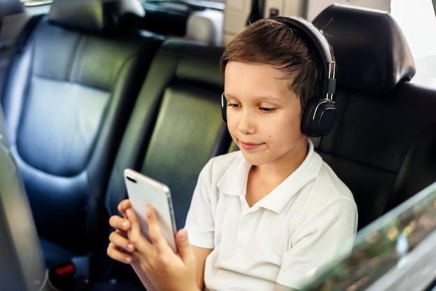 Junge, der auf einem smartphone im auto spielt