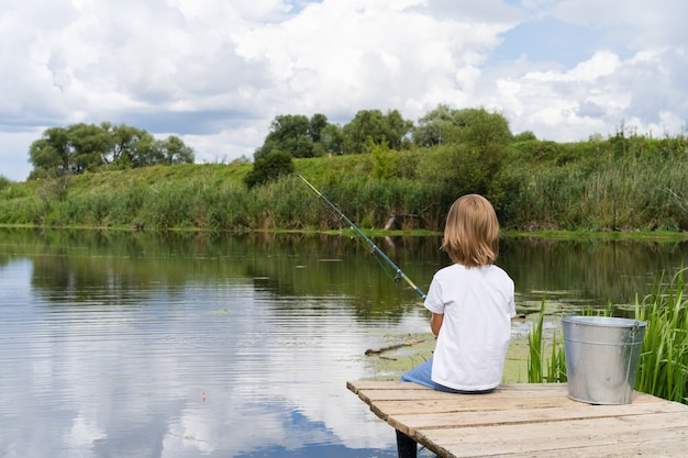 Junge, der auf einer hölzernen brücke nahe einem teich fischt
