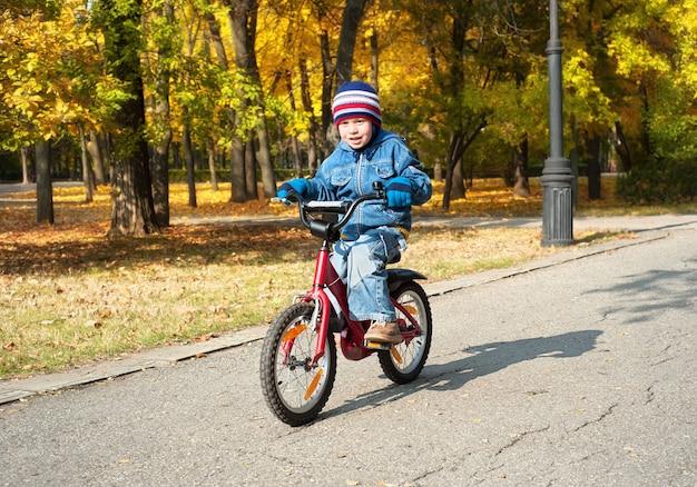 Junge, der auf fahrrad im park reitet