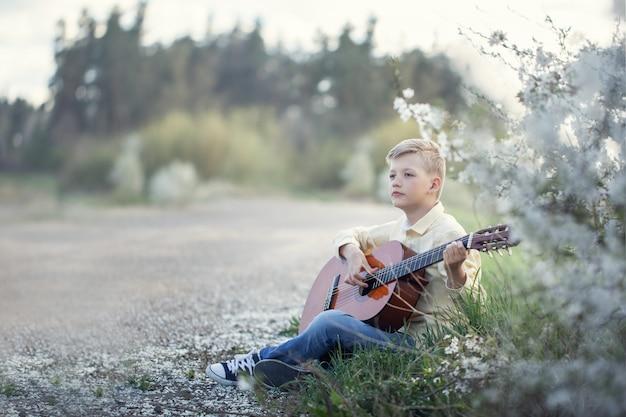 Junge, der auf gitarre im freien spielt