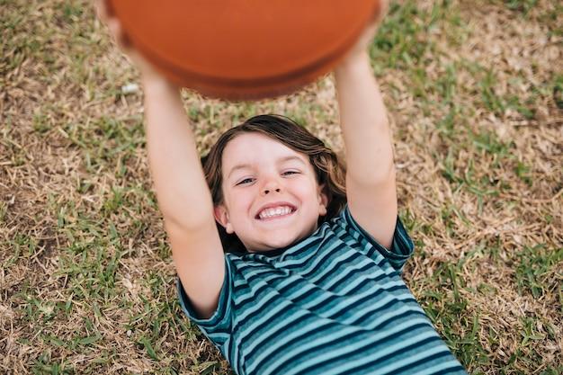 Junge, der auf gras liegt und ball hält