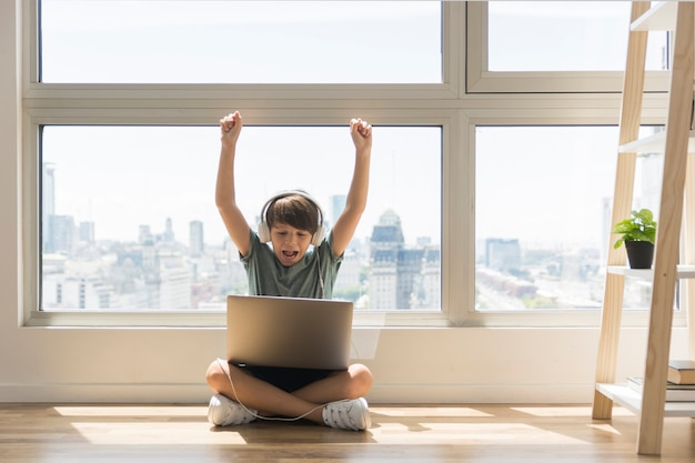 Junge, der auf laptop spielt