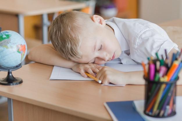 Junge, der auf schreibtisch im klassenzimmer schläft