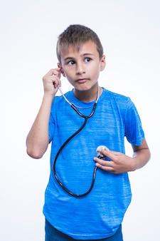 Junge, der auf seinen herzschlag mit stethoskop hört