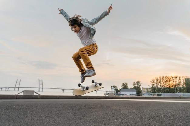 Junge, der auf skateboard an der straße springt