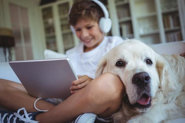 Junge, der auf sofa mit haustierhund sitzt und musik auf digitalem tablett hört