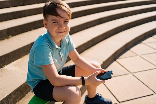 Junge, der auf treppe mit smartphone in seiner hand und grünem penny board sitzt und lustige videos sieht