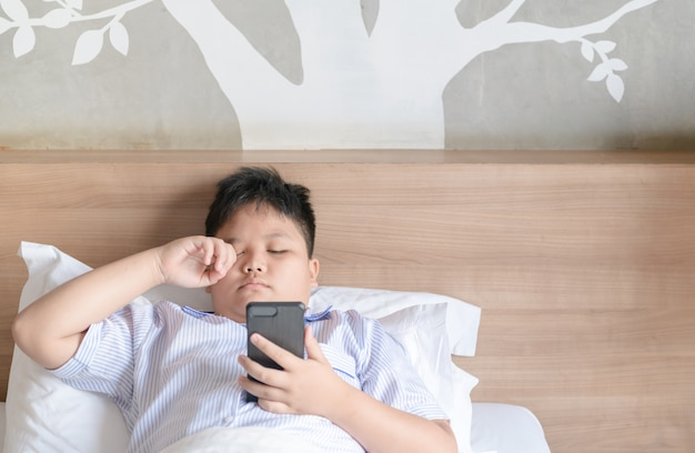 Junge, der augen nach spiel smartphone reibt