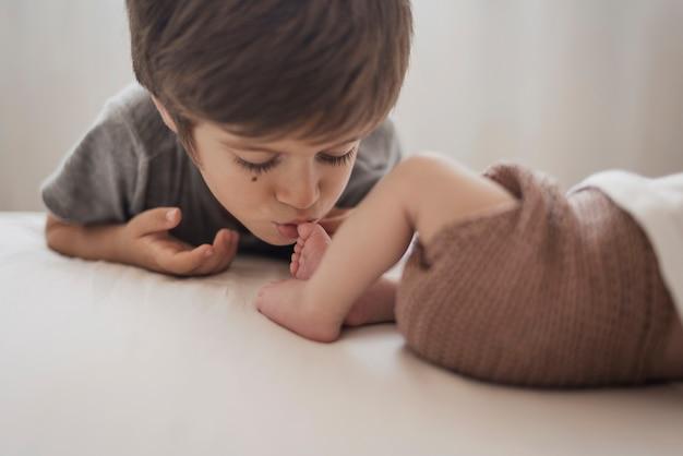 Junge, der bein des kleinen bruders küsst