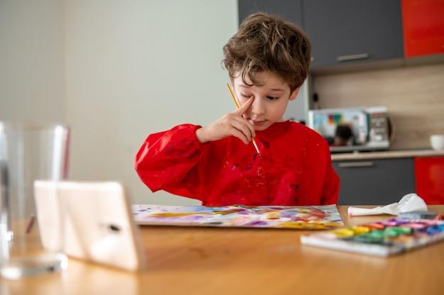 Junge, der bilder zu hause mit online-fernunterricht zeichnet