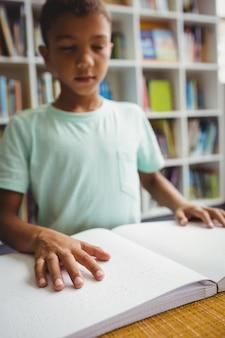 Junge, der blindenschrift verwendet, um zu lesen