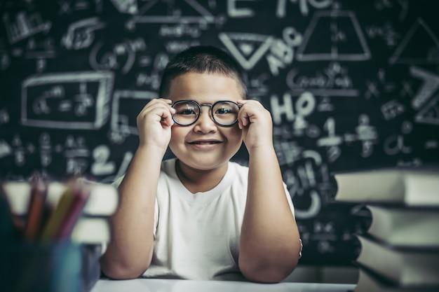Junge, der brillenbein im klassenzimmer studiert und hält.
