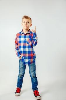 Junge, der buntes kariertes hemd, blue jeans, die gummiüberschuhe, zeigend oben lokalisiert trägt. copyspase.